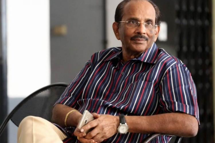 KV Vijayendra Prasad is seated and looking to his left He is dressed in a blue white and red striped shirt and holds a mobile phone in his hands folded on his lap