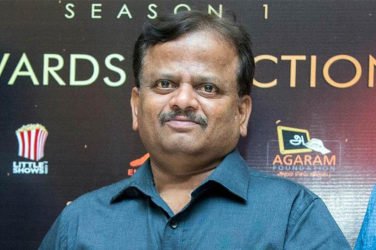 KV Anand in blue shirt at an award function