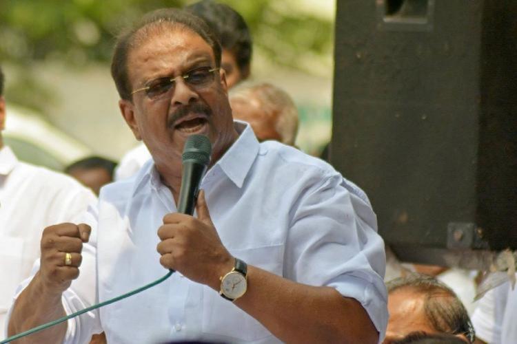 Kerala Congress Leader K Sudhakaran holding a mike speaking at a meeting