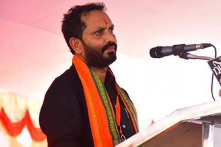 Surendran in black shirt and saffron shawl stands before a microphone and talks the profile is sideways and the background is pink