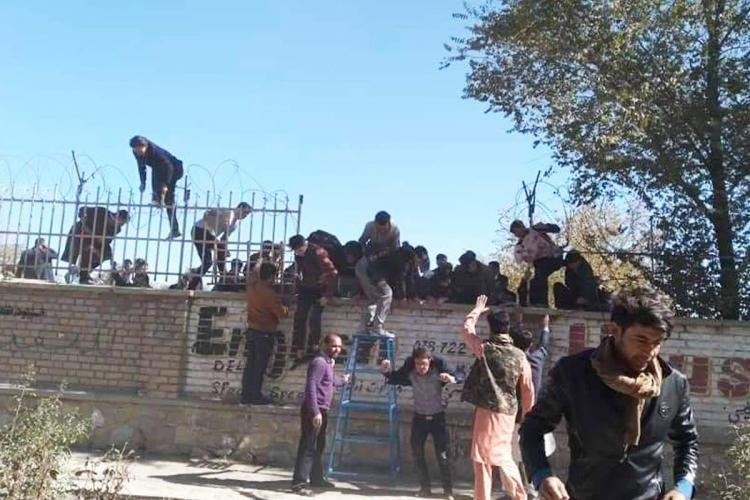 A screengrab from a video captured during the Kabul University shooting shows students scaling the walls of the campus to escape the attack