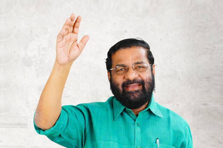 Kadakampally in a copper sulphate blue-green shirt raises a hand and waves smiling standing against a white background