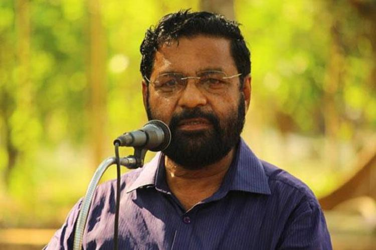Kerala Minister Kadakampally Surendran in a blue shirt standing and facing a mike