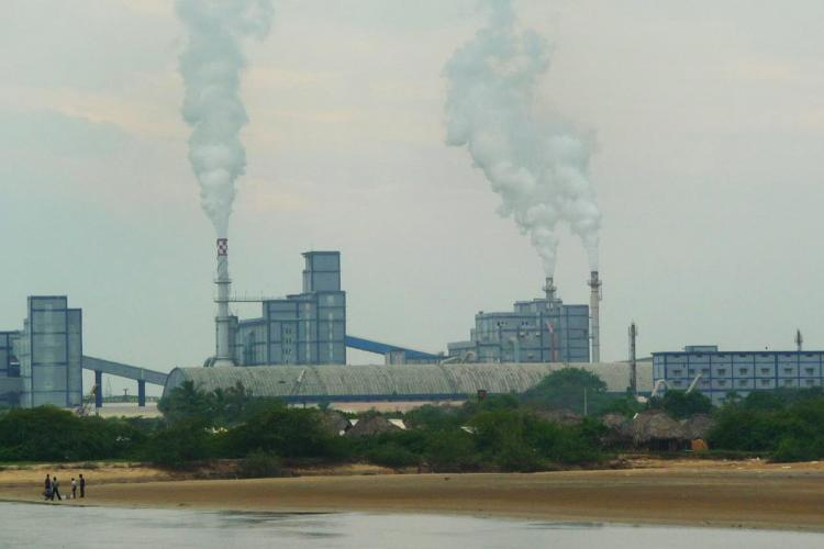 Plumes of smoke emitting from a factory unit near the Kakinada Beach in Andhra Pradesh A small group of people are seen standing near the lake close to the factory