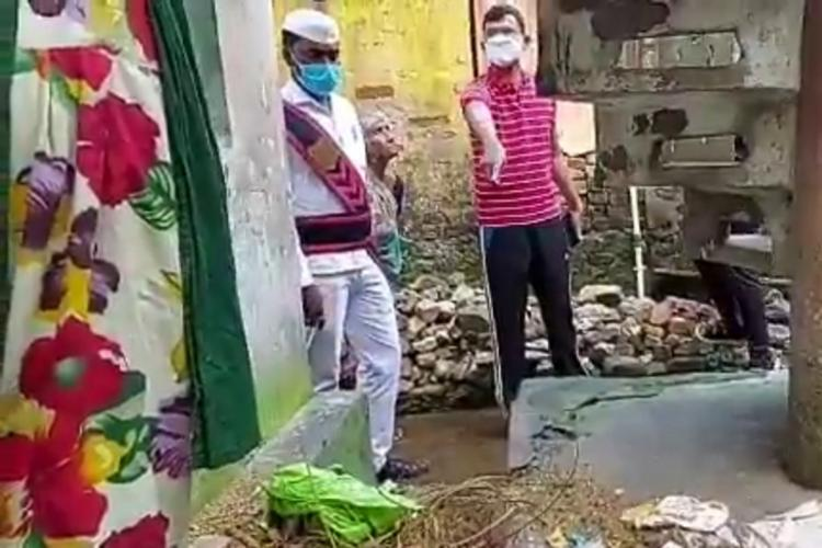 Kakinada Municipal Commissioner pointing to garbage in front of a womans house as she stands and watches municipal workers are standing to the side