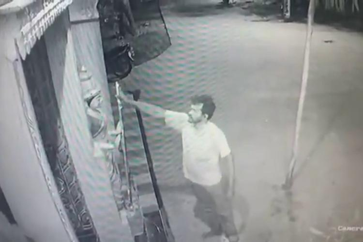 CCTV footage of a man standing in front of an idol holding the trident belonging to the deity