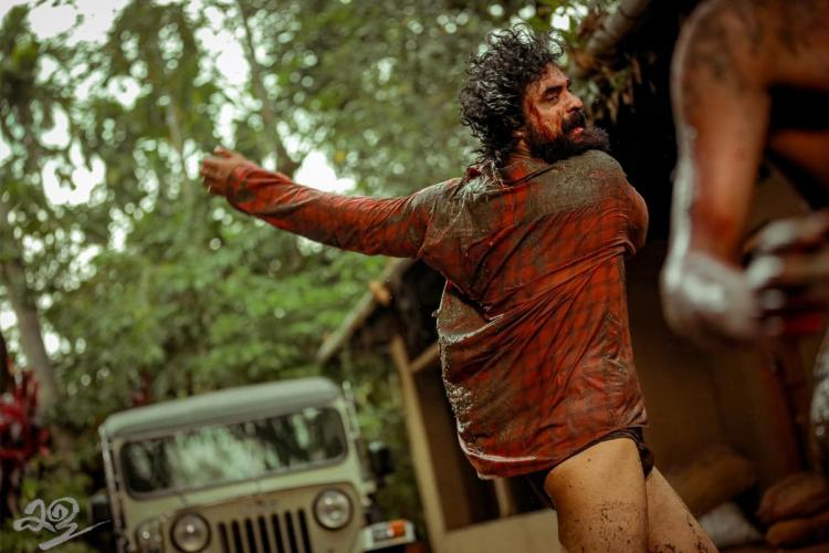 Tovino in a fight wearing a brown shirt and hitting out with his hands while in the background are trees and a jeep