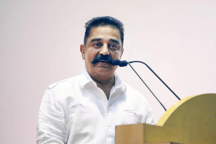 Kamal Haasan speaks into a mic and looks partially to the left