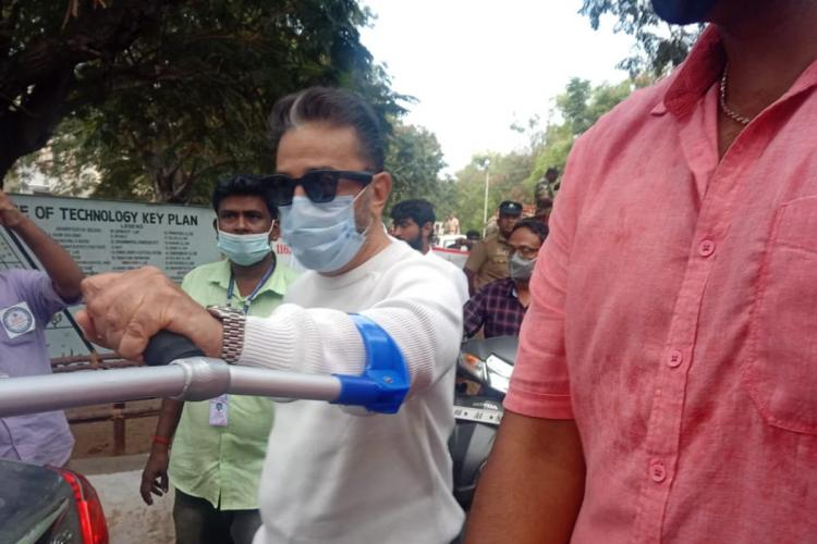 Kamal Haasan raises a walking stick against a reporter not in the frame in Coimbatore