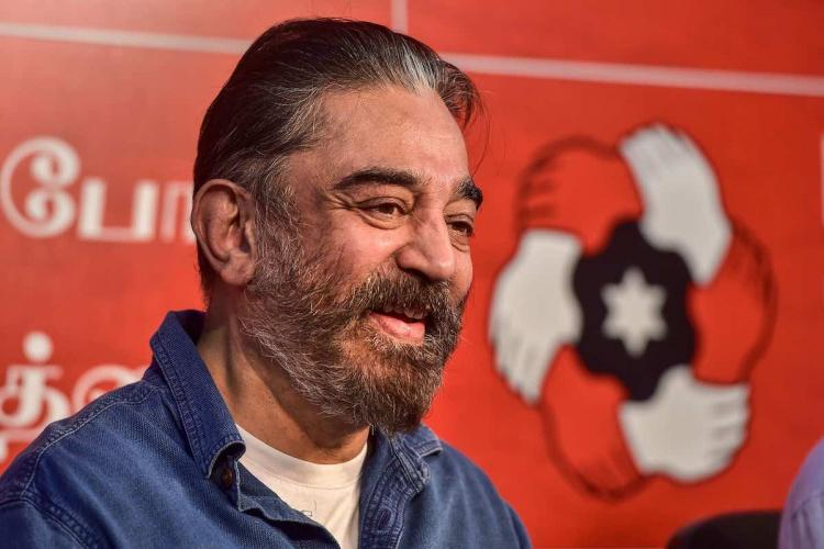 Kamal Haasan looks happy and cheerful at a political meeting with his party's banner seen in the background