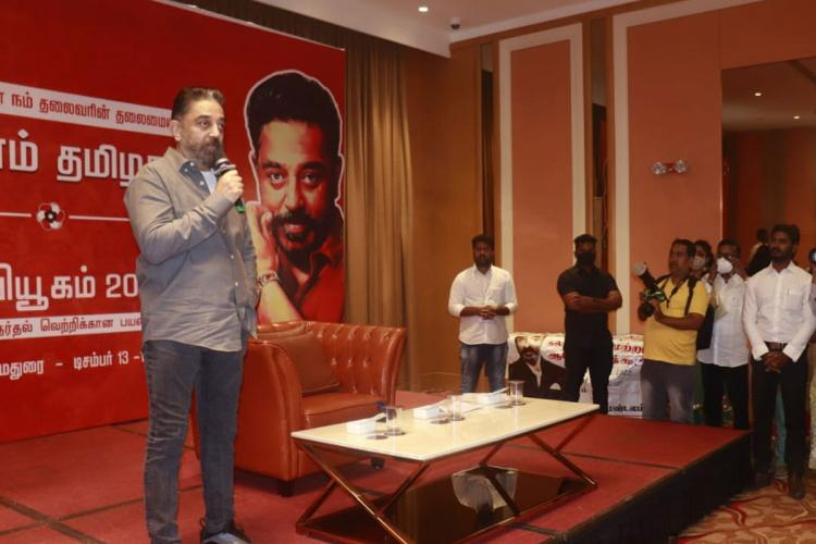 Kamal Haasan stands before the media in Madurai holding a microphone as people gather to the right