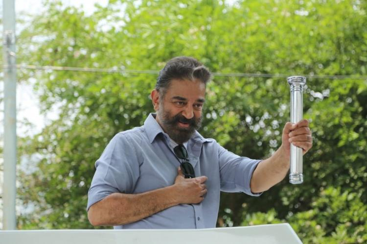 Makkal Needhi Maiam (MNM) chief Kamal Haasan wearing a light blue shirt and holding up a torch in his left hand