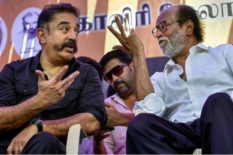 Rajinikanth and Kamal Haasan talking to each other on a stage