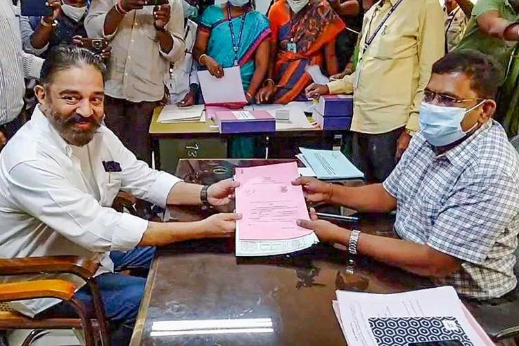 Kamal Haasan handing over his nomination papers to the returning officer both posing for camera