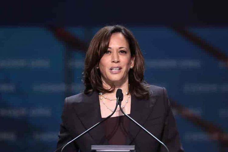 California Senator Kamala Harris stands at a podium in front of a microphone