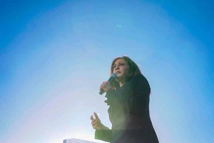 Kamala Harris with mic amid blue sunny sky