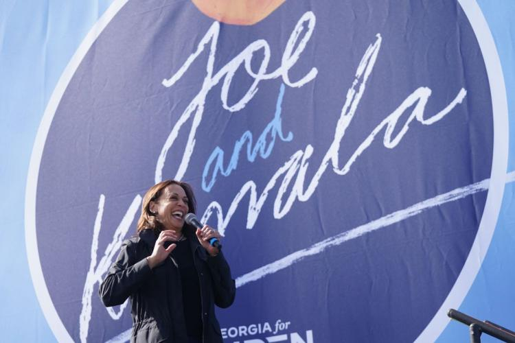 Kamala Harris in front of blue banner looking happy