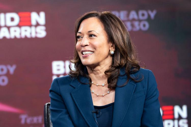 Kamala Harris wears a blue suit and smiles for the crowd
