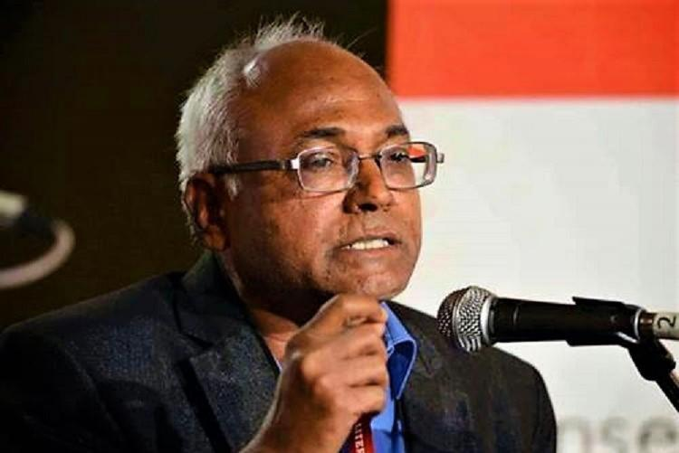 Kancha Ilaiah gesticulates with his right hand as he speaks into a mic