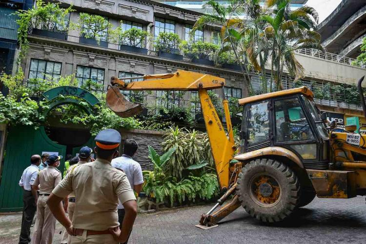 Kanganas bunglaow in Mumbai being demolished by BMC An earthmover is seen demolishing the building A few police officials are seen in the image