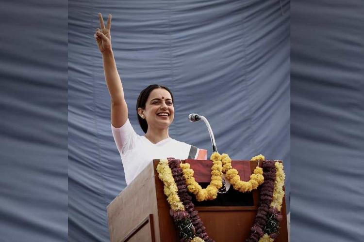 Kangana Ranaut in Thalaivi waving from a podium wearing a white saree