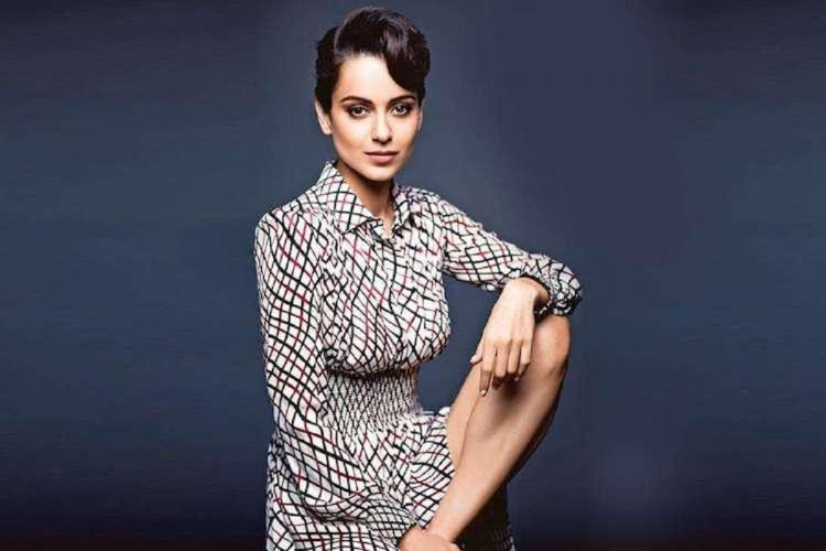Kangana Ranaut sitting IN front of a blue wall