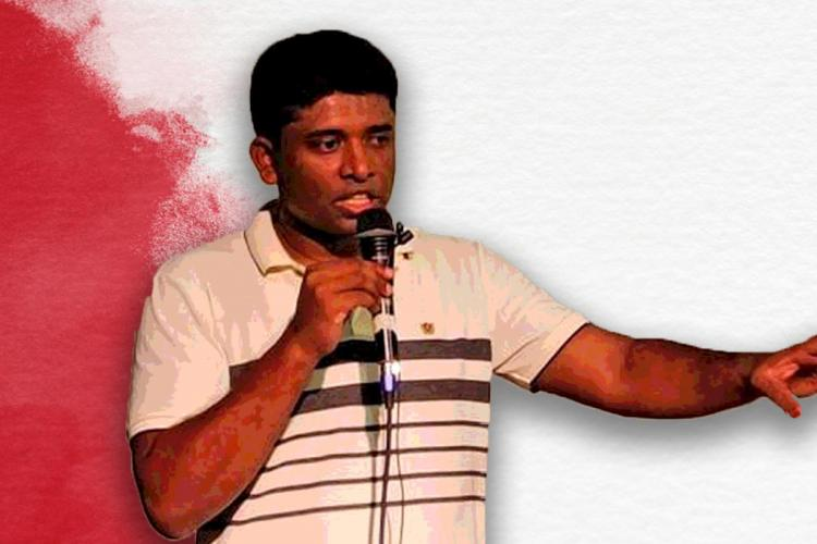 Kannan Gopinathan speaking at an event He is wearing a white t-shirt with stripes and is holding a mic