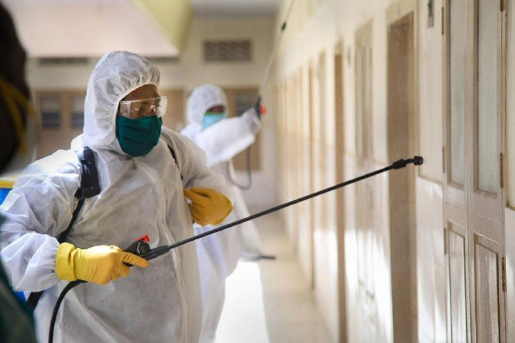 Man in a PPE suit disinfecting a wall