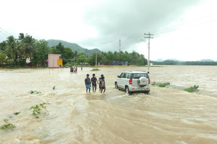 People walking on a flooded road after heavy rains in Kanyakumari