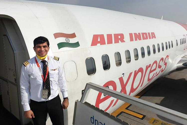 Akhilesh Kumar standing at the entry door of an Air India Express flight He is smiling and is seen in his uniform and yellow mask lowered on his neck