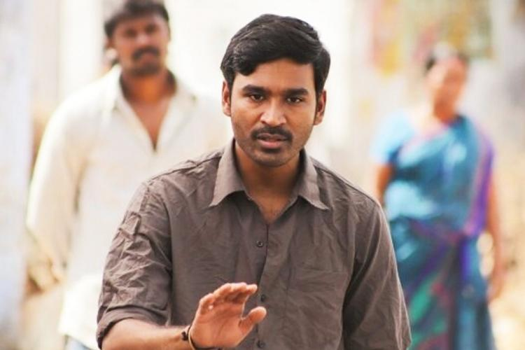 Dhanush as Karnan in Mari Selvarajs film wearing a grey shirt and holding his hand up in protest