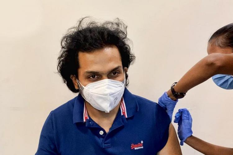 Actor Karthi wearing a blue shirt taking his COVID-19 vaccine shot