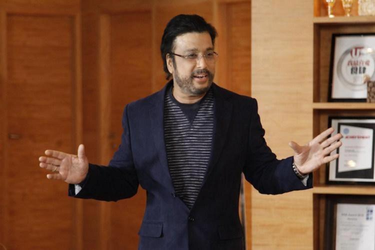 Actor Karthik wearing a black suit and gesturing with his hands