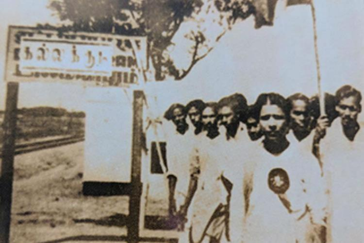 A young Karunanidhi and a group of DMK cadre stand before the Dalmiapuram railway station signboard during the Kallakudi agitation