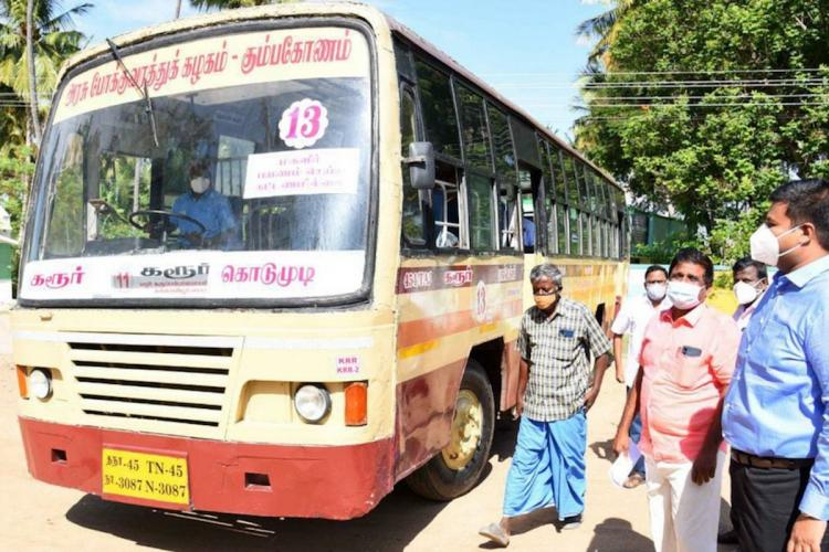 A new red and off-white Tamil Nadu public bus parked with people standing next to it