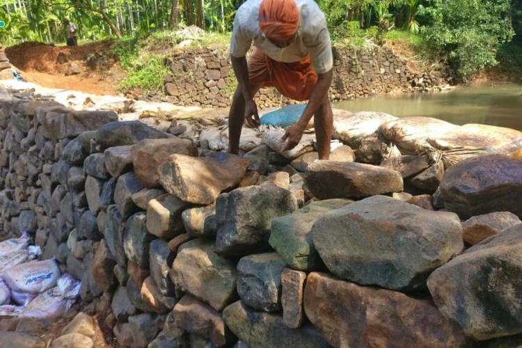 A man constructing a temporary check dam katta in Yethadukka