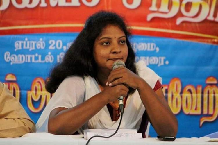 Journalist Kavin Malar holds a mic, and speaks looking towards the right.