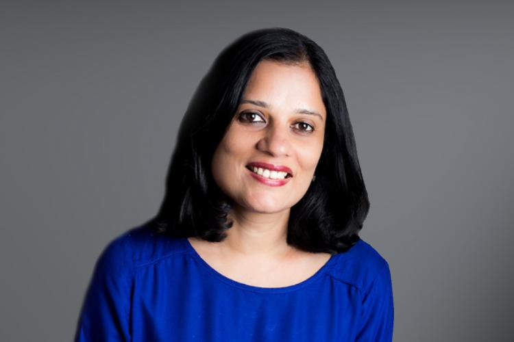 Author Kavitha Rao in a blue dress standing in front of a grey background