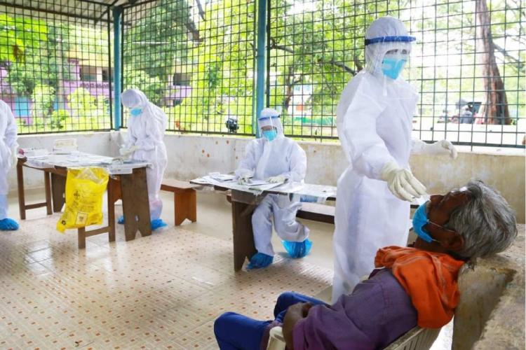 Three healthcare workers covered in white PPE kit can be seen in a room where one of them collects swab from a grey-haired man sitting down wearing blue clothes