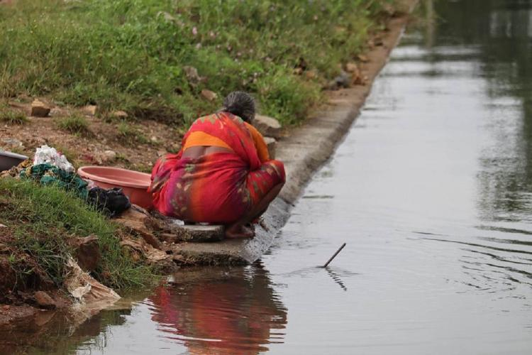 A woman wearing a red sari is washing clothes by a riverside She is turned the other way and is sitting on the side