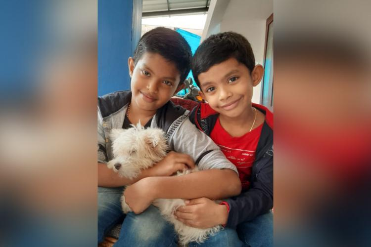 Two young boys holding a dog