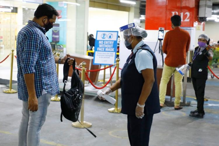 A staff sanitising a visitors bag at a mall