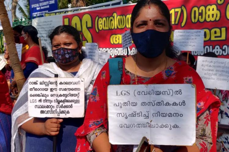 Two women hold placards during a protest by PSC rank holders outside the Secretariat in Kerala