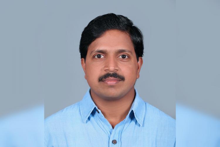 Kerala professor Gilbert Sebastian in a blue shirt.