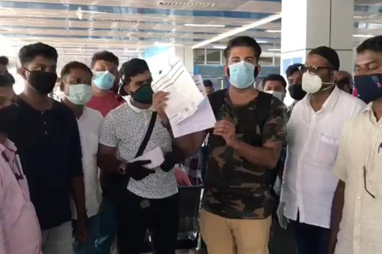 A man in face mask holds up a a medical report, while others are standing around him. The group of men, all wearing masks, are at an airport.