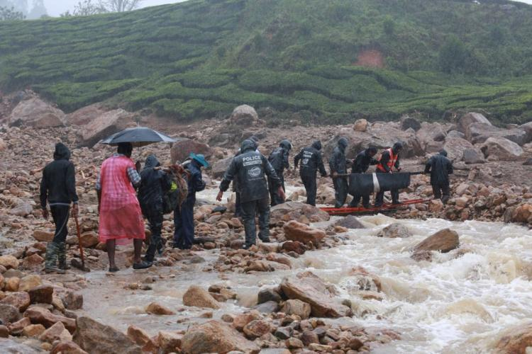 Rescue operations to find the bodies of Pettimudi landslide victims underway Rescue workers in black raincoats and boots are trudging along rivers and debris carrying a body in a stretcher