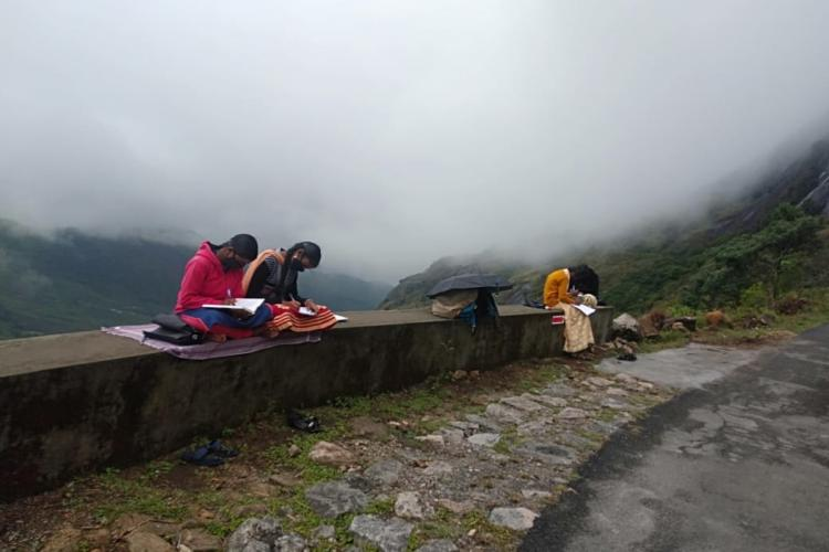 Students sit in the Eravikulam National Park to attend online classes
