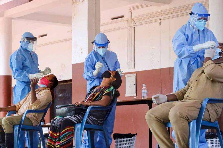 Three health workers in PPE collecting swab samples from people