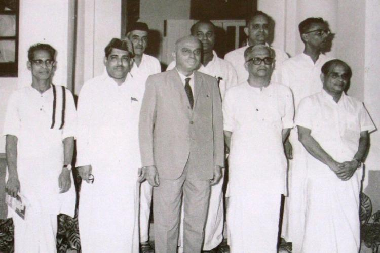 Black and white photo of ministers in 1969 nine men stand in two rows with one of them wearing a suit and the others mundu and shirt