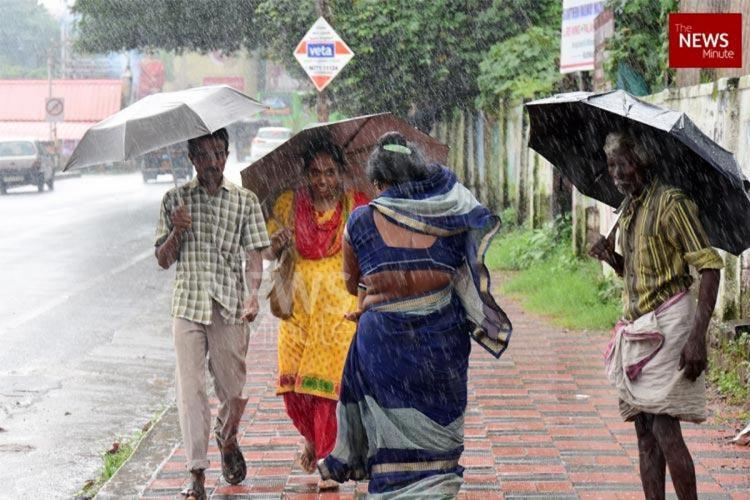 On a rainy day in monsoon, people walk on pavement with umberalla